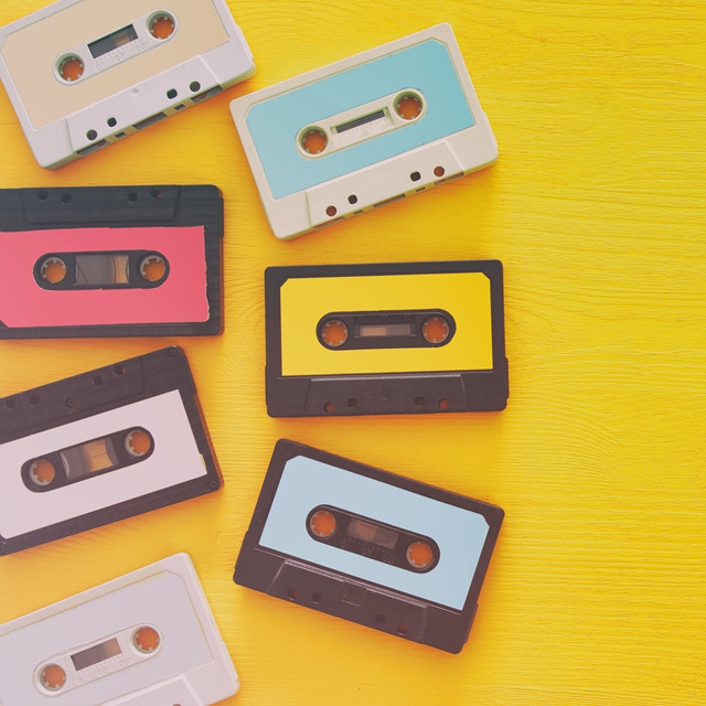 Retro cassette tape collection over yellow wooden table. top view. copy space.